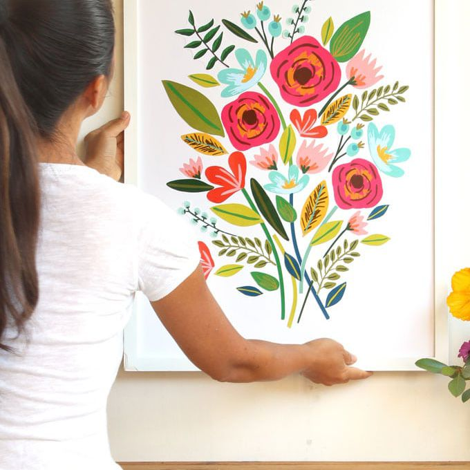 Woman hanging floral wall art