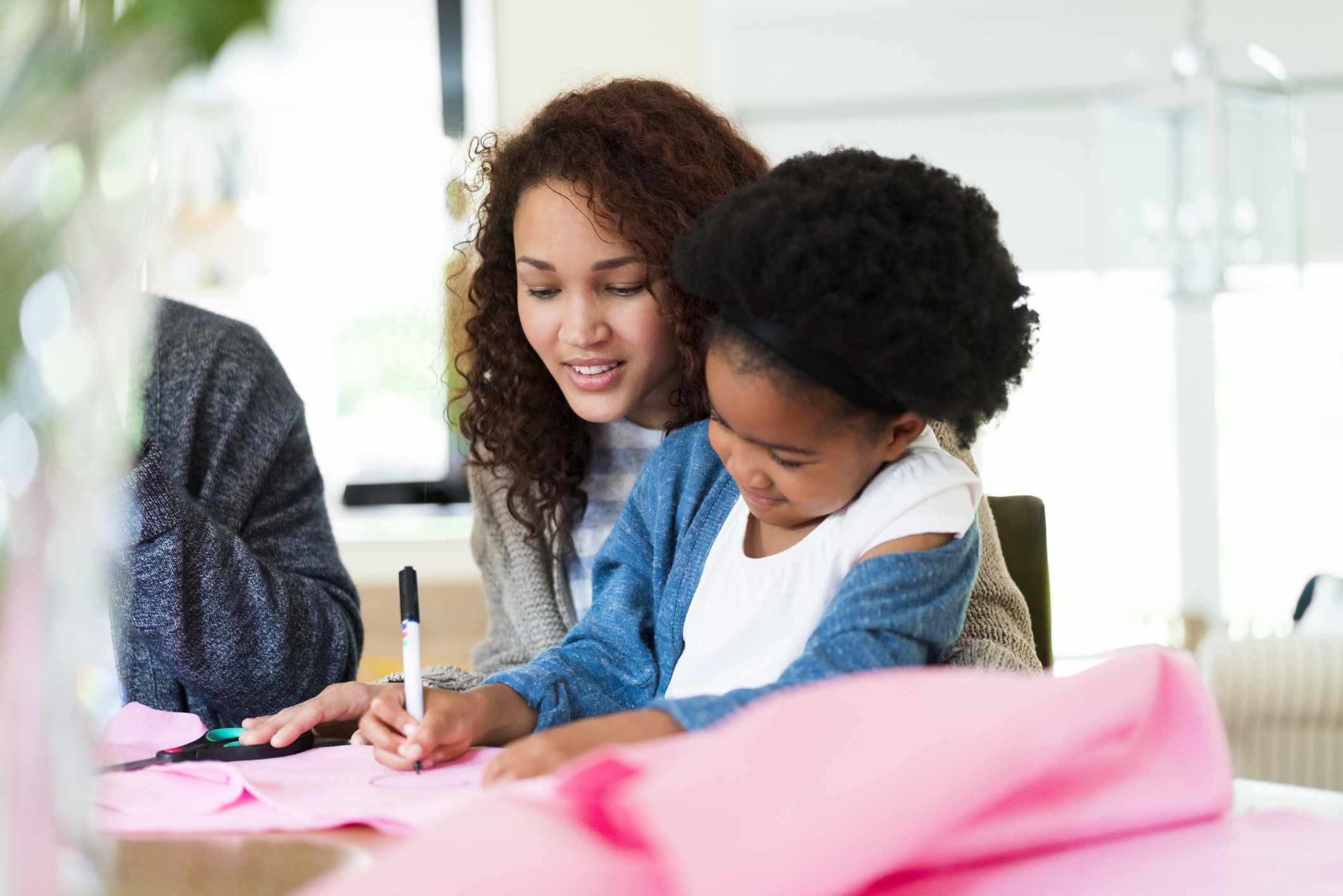 Woman looking at girl drawing on fabric at home