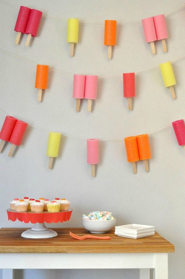 Pool noodle Popsicles hanging on a wall with a tray of cupcakes on a wooden table.