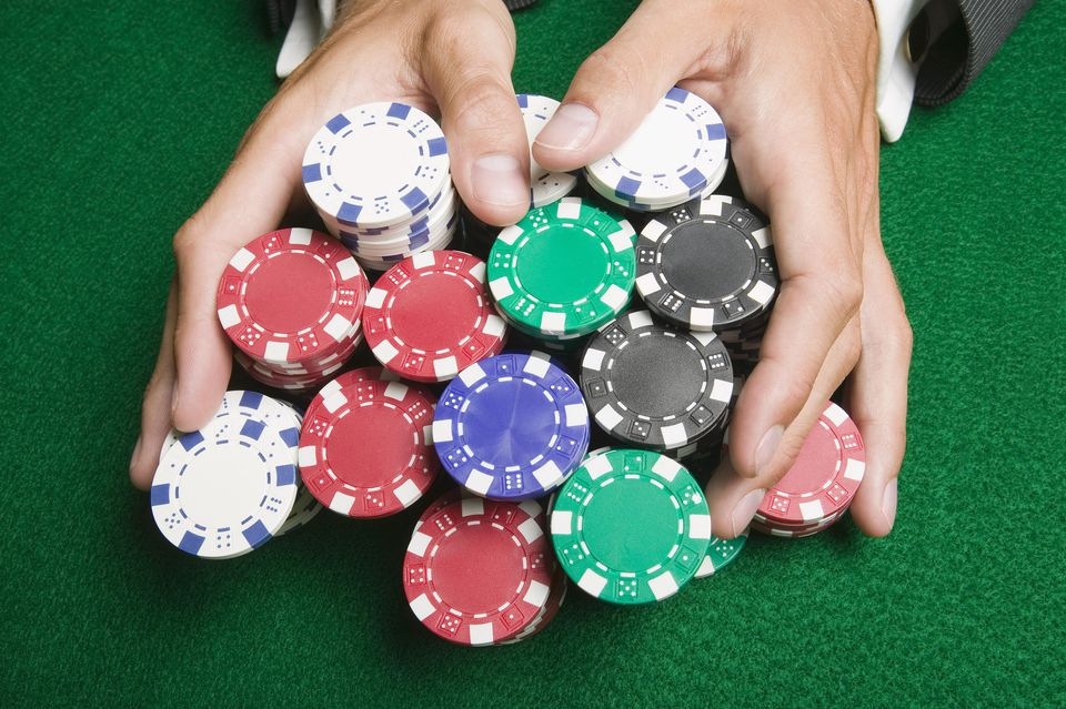 Man pushing large stack of poker chips across gaming table, close-up