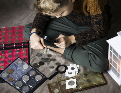 boy numismatist collects old coins, an album with coins