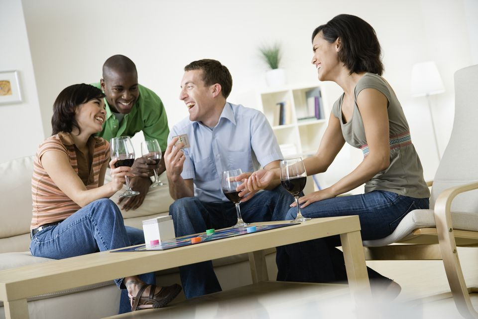 Four young people sitting in living room at home, drinking wine, laughing and playing board game