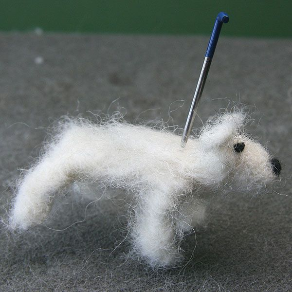 The head of the felted dog is needle felted to the body at the neck edge.