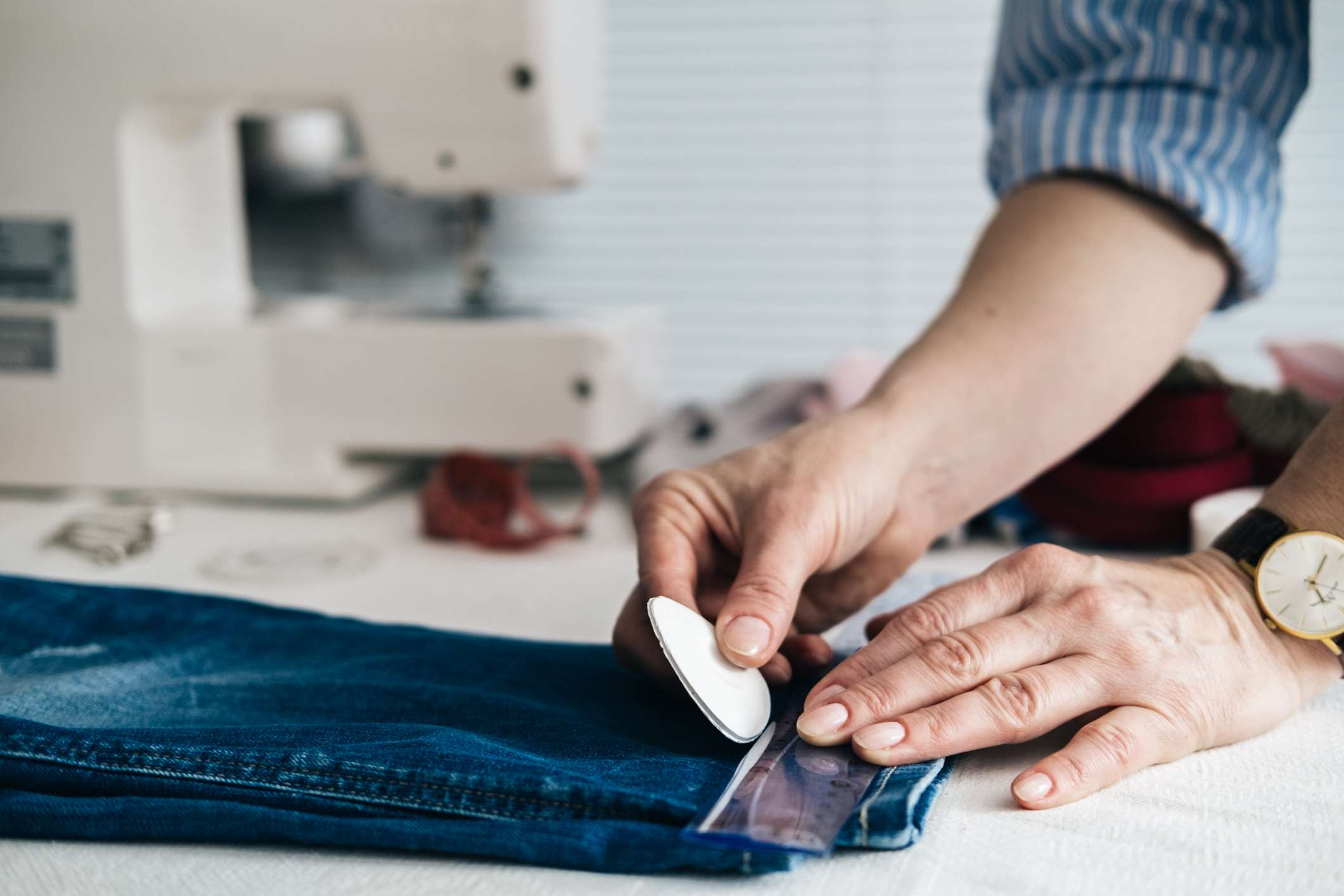 Seamstress marking hem on a pair of jeans in tailor shop