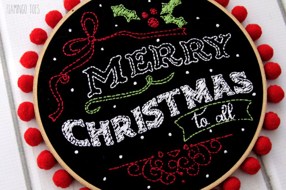 Merry Christmas chalk art embroidery pattern on black fabric and placed in an embroidery hoop.