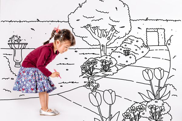 Little girl drawing a park on white background