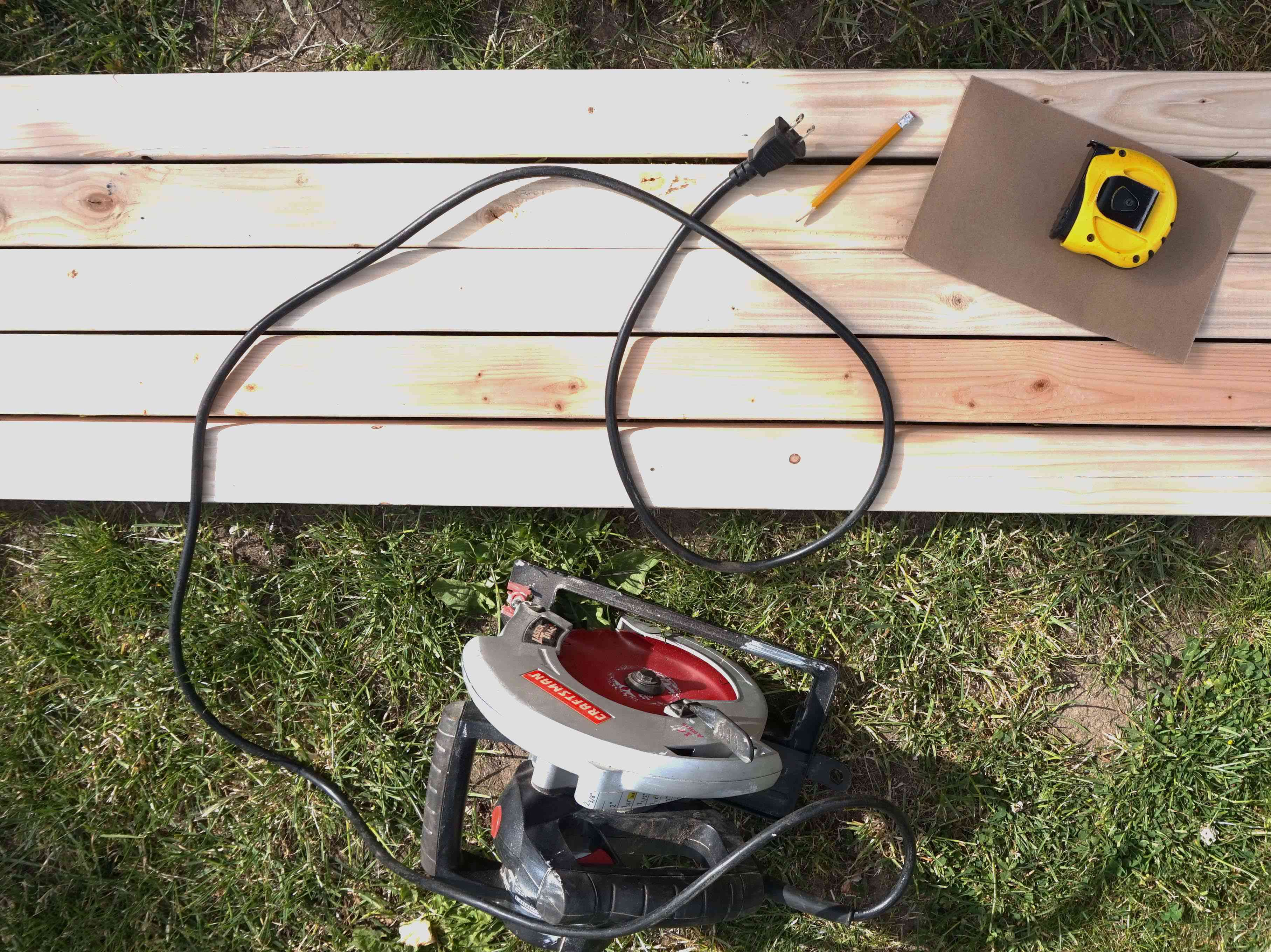 A saw, wooden boards, piece of sandpaper, pencil and tape measure sitting on the grass