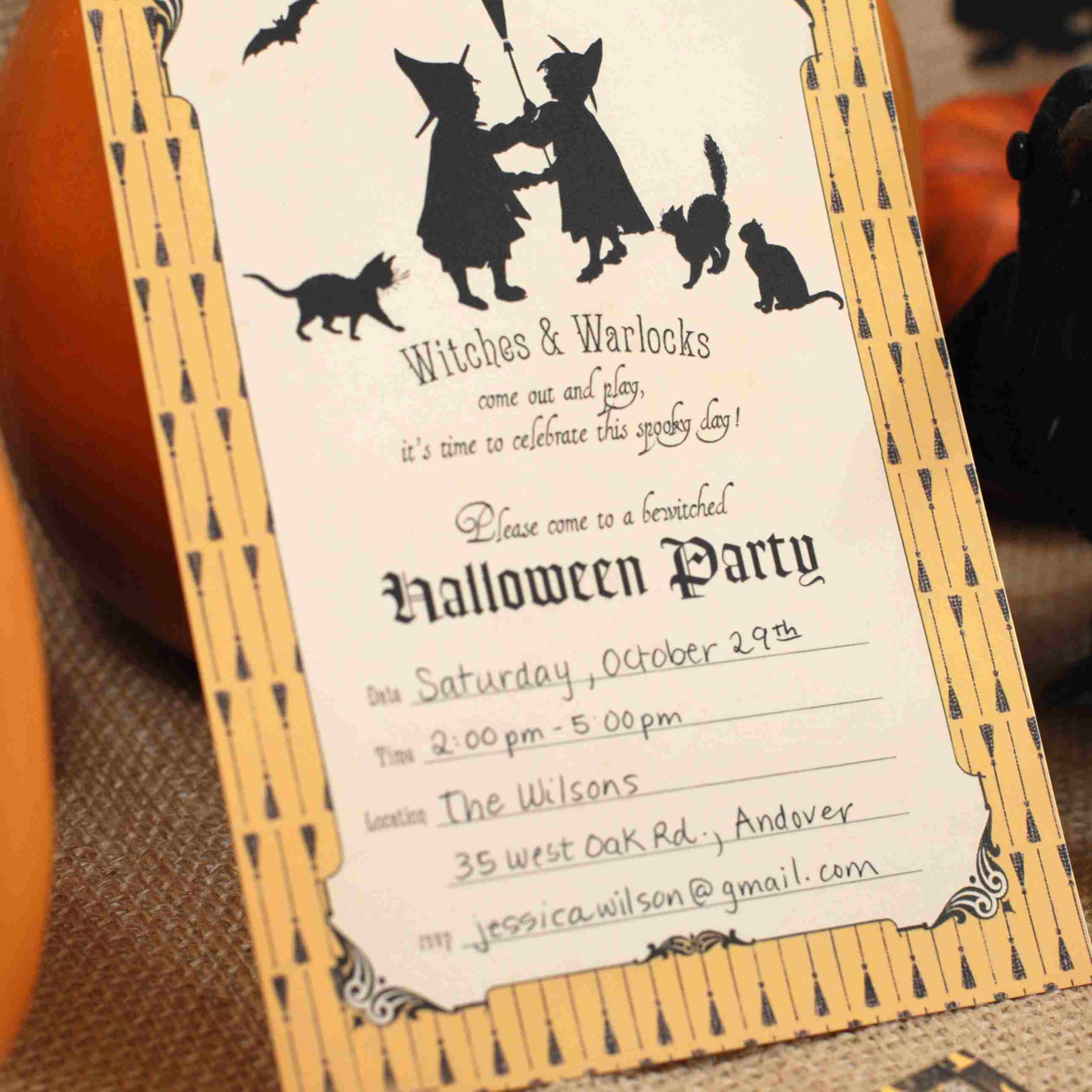 A Halloween Party Invitation Standing Up Against Pumpkin