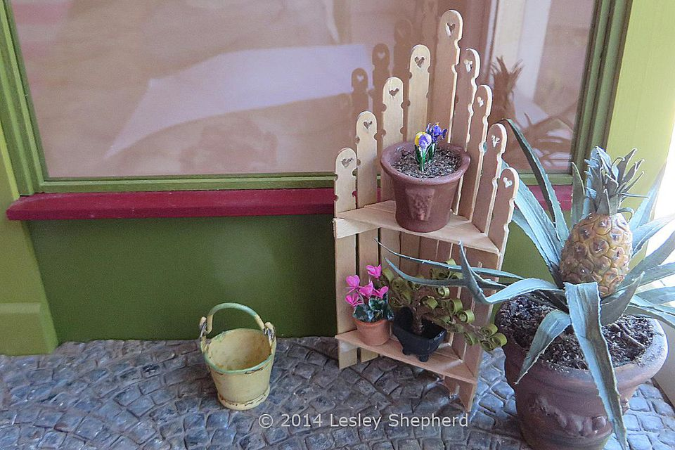 Shabby chic corner shelf unit made from dollhouse scale fence pickets.