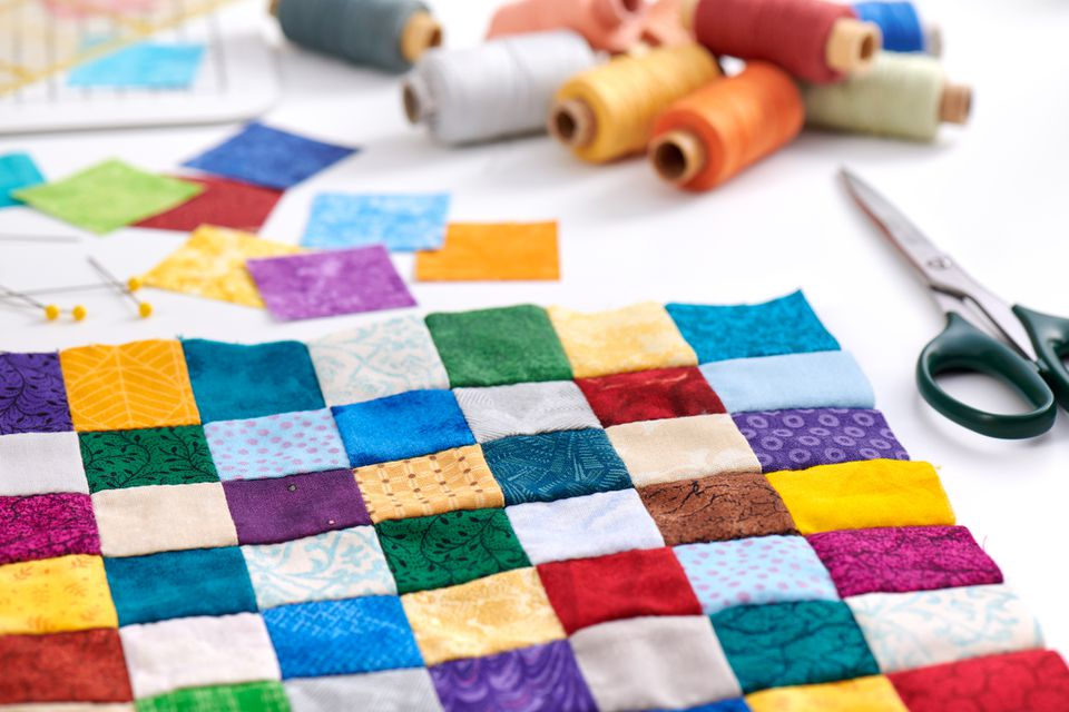 Colorful part of quilt sewn from square pieces, spools of thread, scissors, quilting and sewing accessories