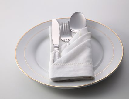 High Angle View Of Eating Utensils And Napkin In Plate On White Background