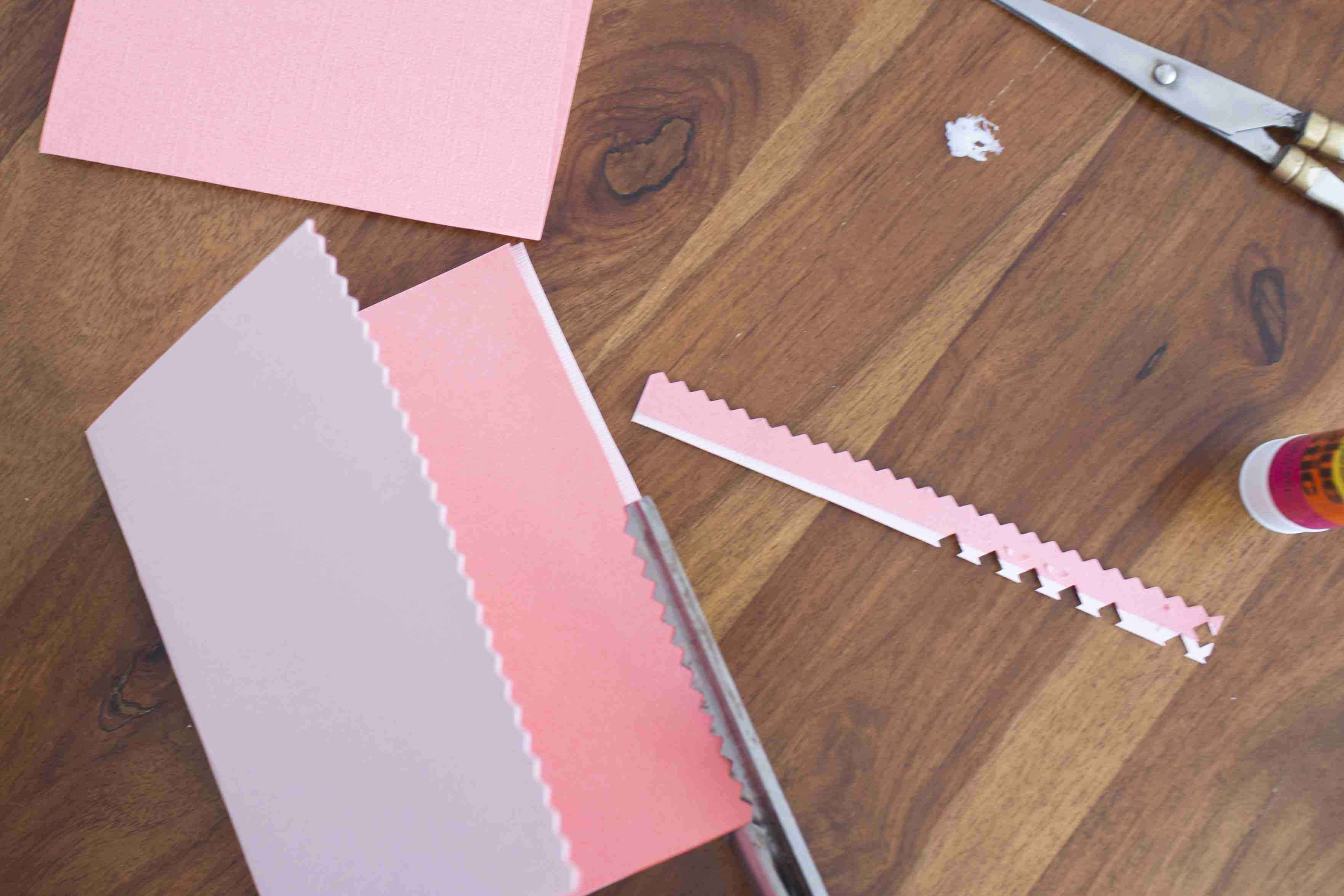 Cardstock being cut with pinking shears