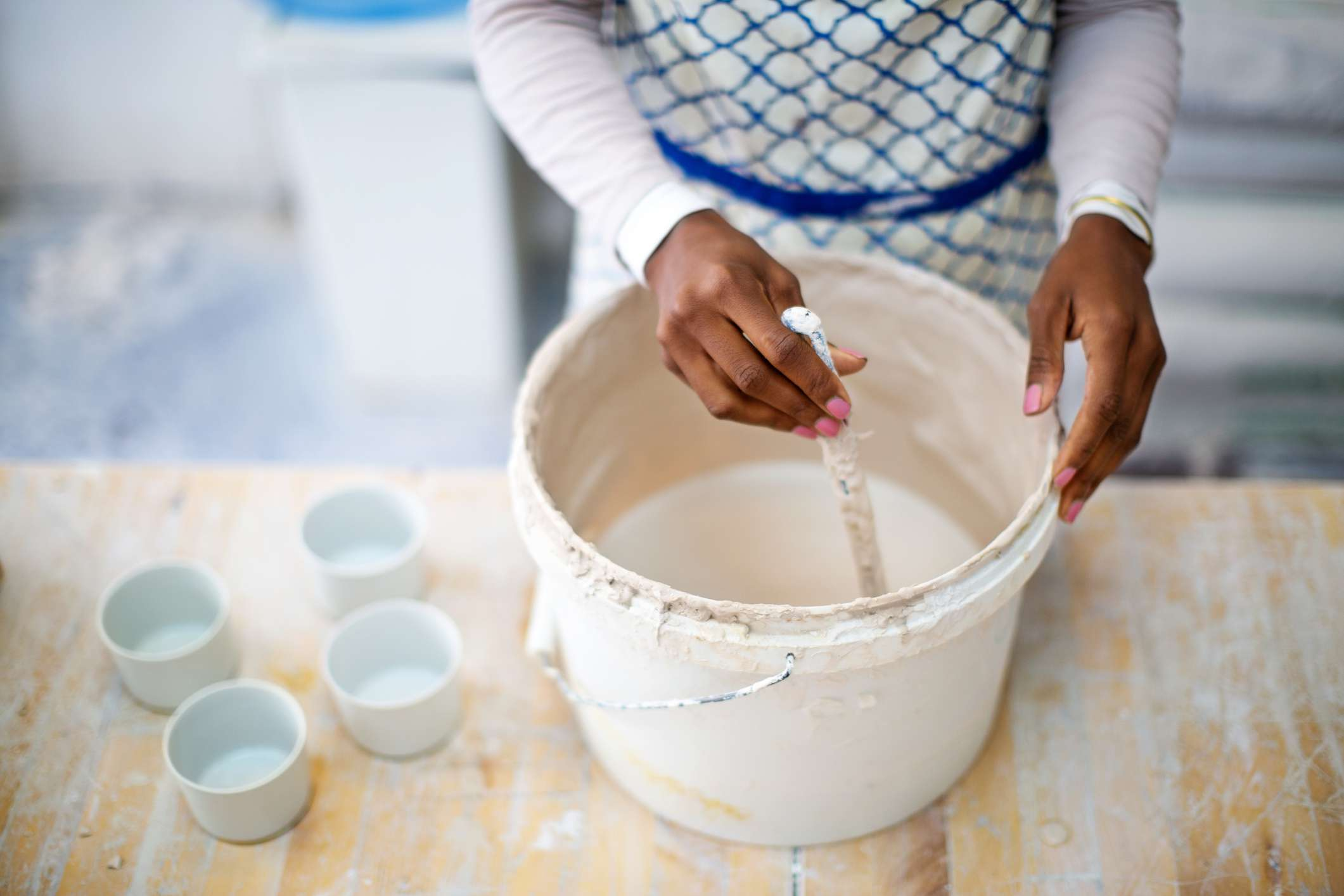 Potter mixing pottery mixture in a bucket at workshop