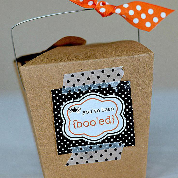 A brown take-out box with a spider on the tag