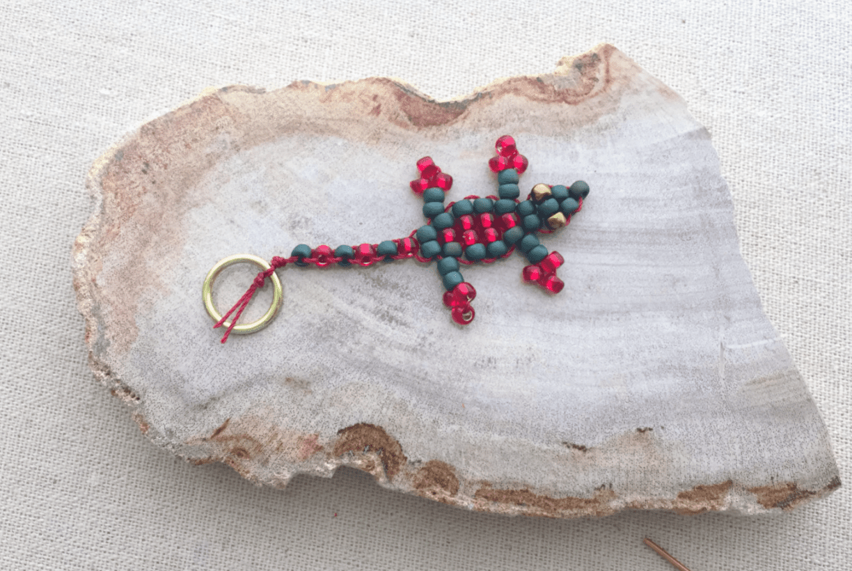 a keychain in the shape of a lizard made of black and white beads