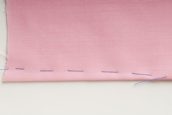 Dart marked out with basting stitch, on pink fabric, close up