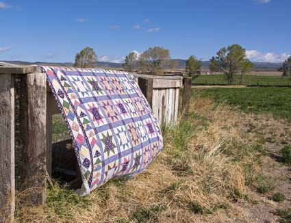 Quilt hanging over a rustic fence