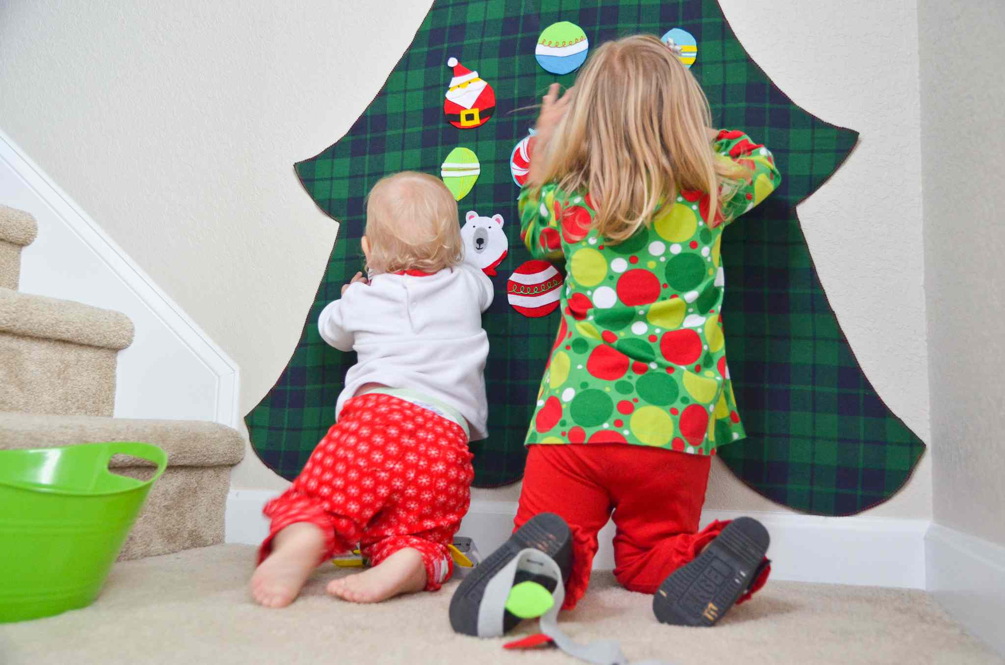 Two kids hanging up felt ornaments on a felt Christmas tree on the wall.