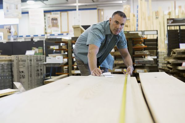 Man measuring wood planks at home improvement store
