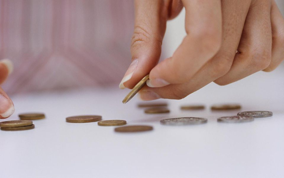 Close-up of a woman's hands sorting coins
