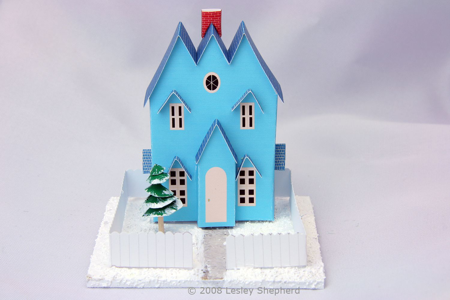 A miniature N scale Putz style cottage on a landscaped base with a tree, fence and snow.