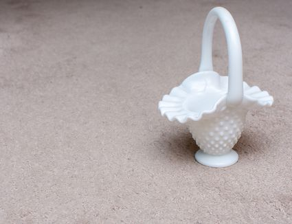 Fenton glass mini vase collection of expensive white glassware with open space on white background.