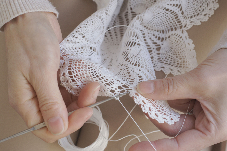 Woman's hand stitching a lace doily.