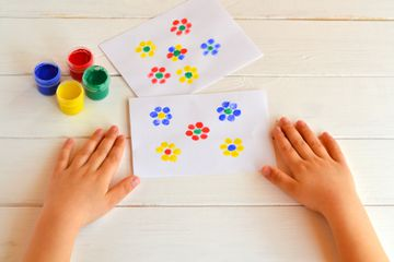 Two paintings of flowers painted children fingers. Jars with gouache. Children hands are on the table. Fingerpainting ideas for kids summer