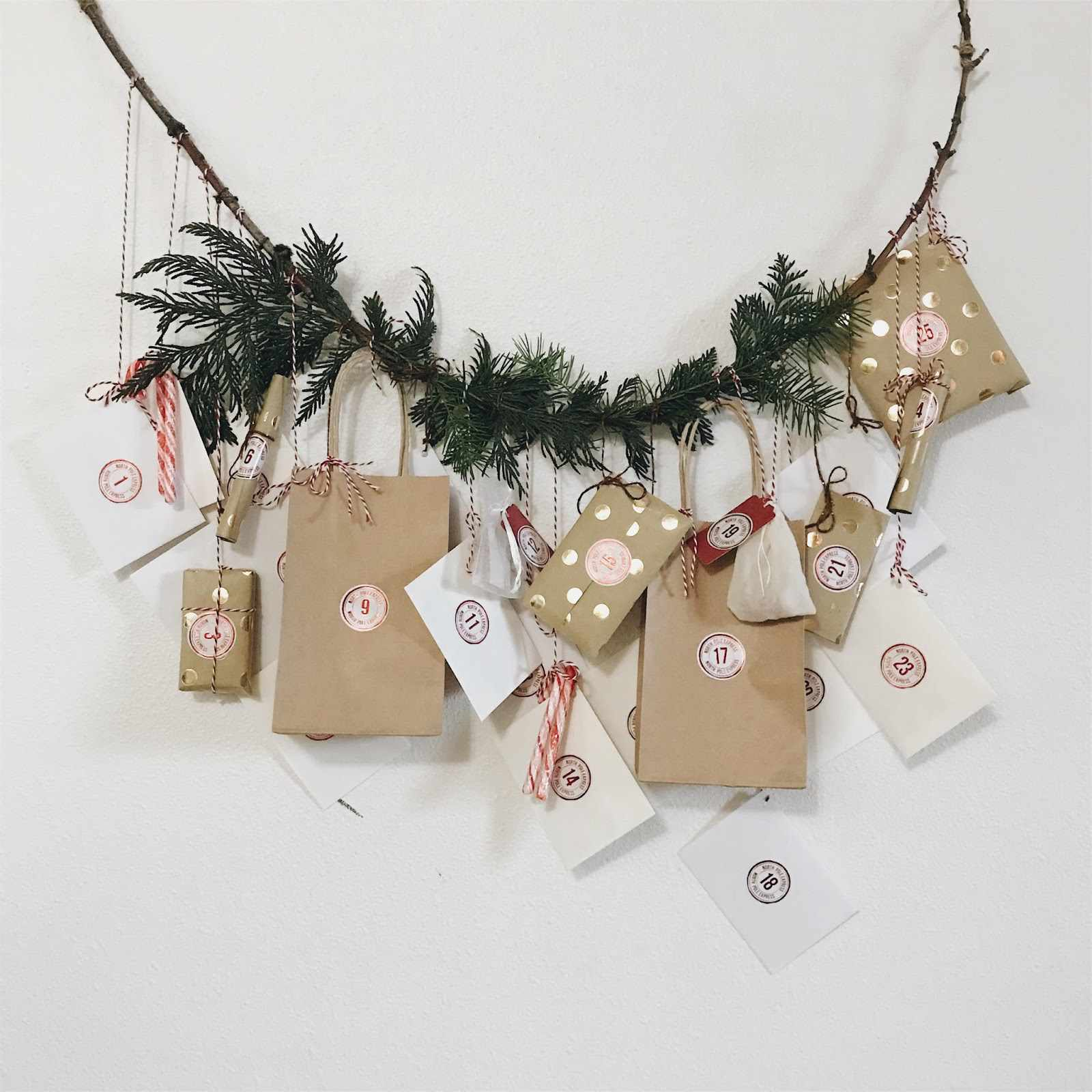 Hanging brown and white packages on a tree branch garland.