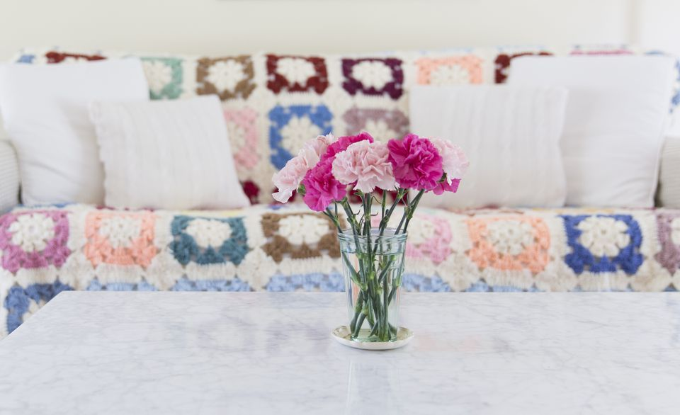 Glass full of pink carnations on coffee table