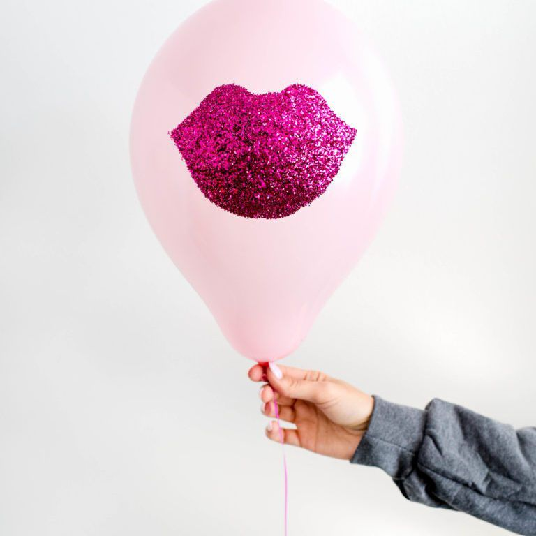 A hand holding a pink latex balloon with hot pink stenciled lips made out of glitter on the balloon