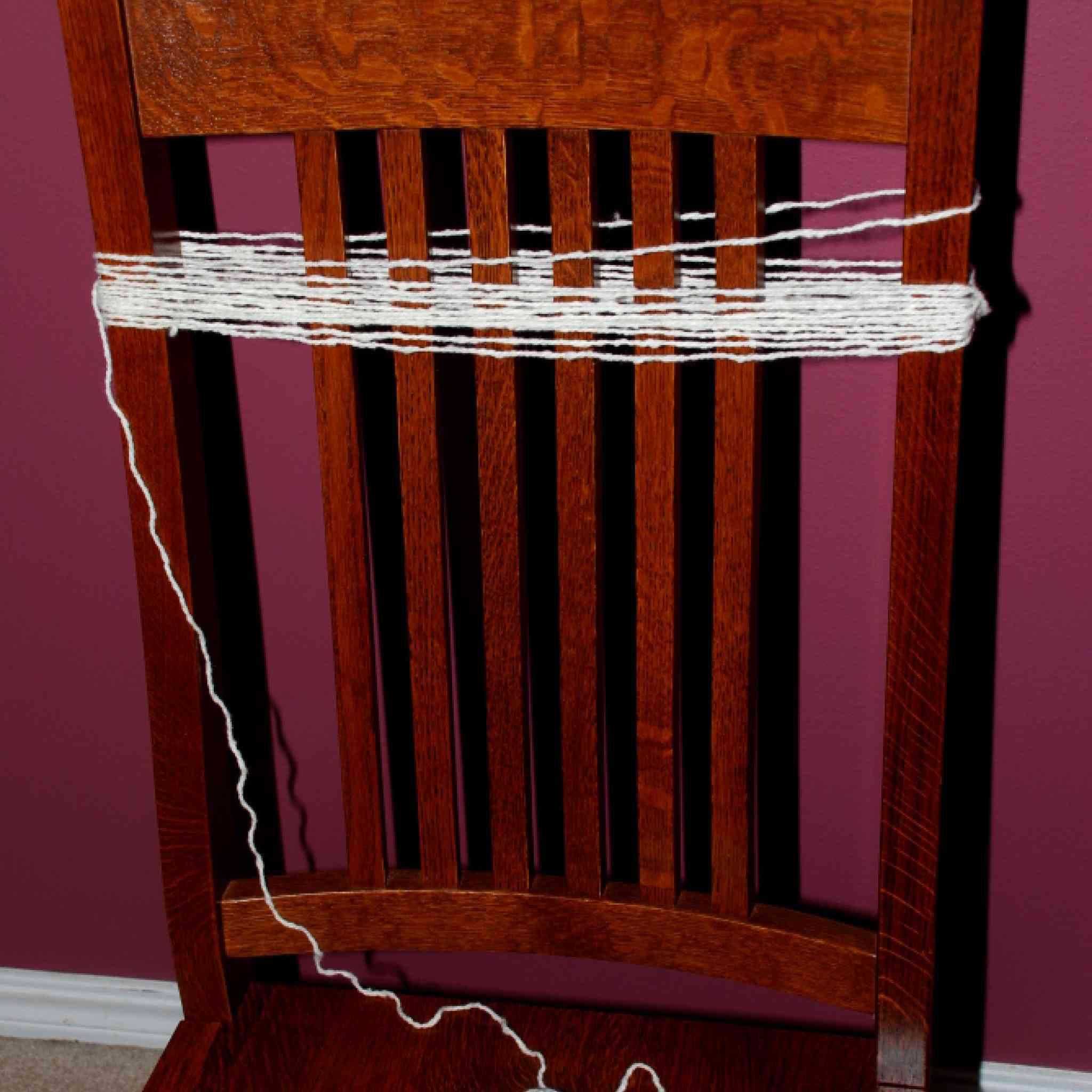 White yarn wrapped around the slats on the chair.