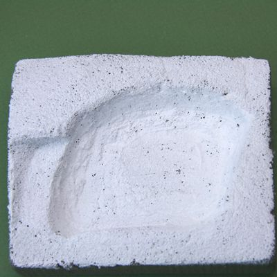 A finished miniature pool recess in florist's foam is coated with a protective coat of acrylic paint