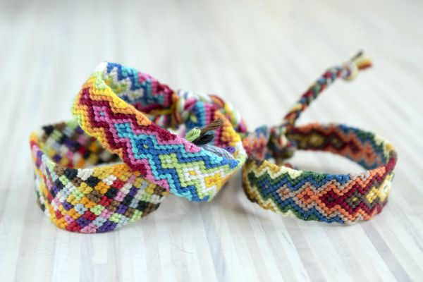 Group of simple handmade homemade natural woven bracelets of friendship on wooden background