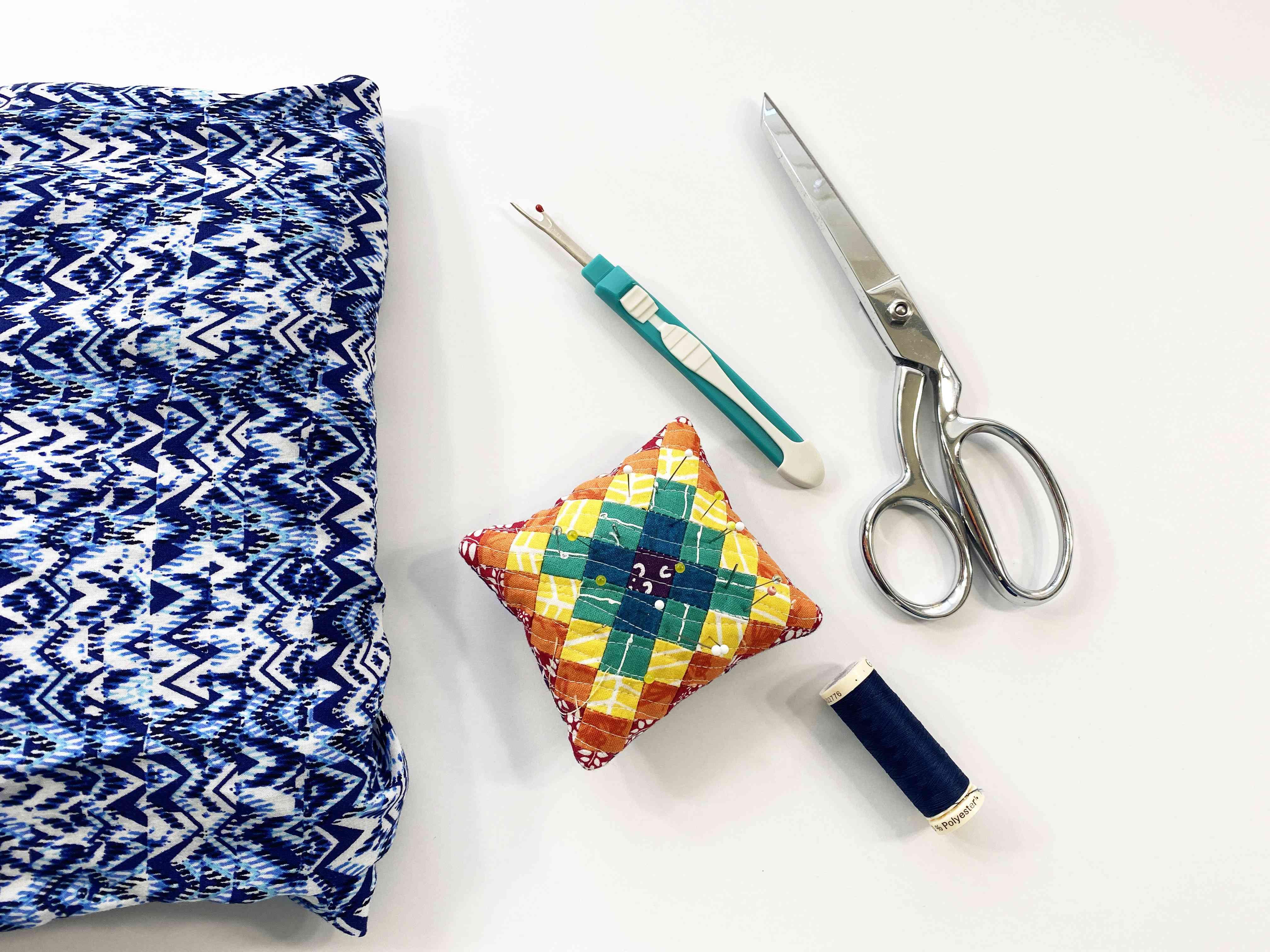 A blouse, pins, seam ripper, scissors, and thread