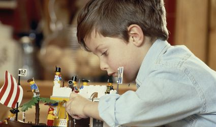 Young boy playing with LEGOs.