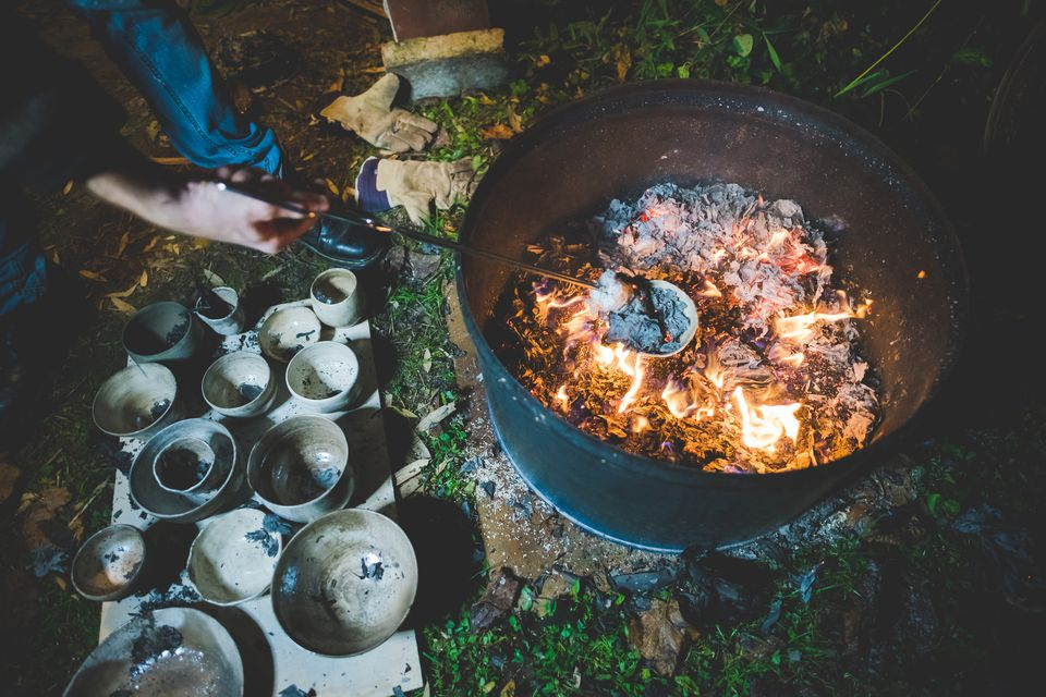 Raku pottery being fired outdoors at night