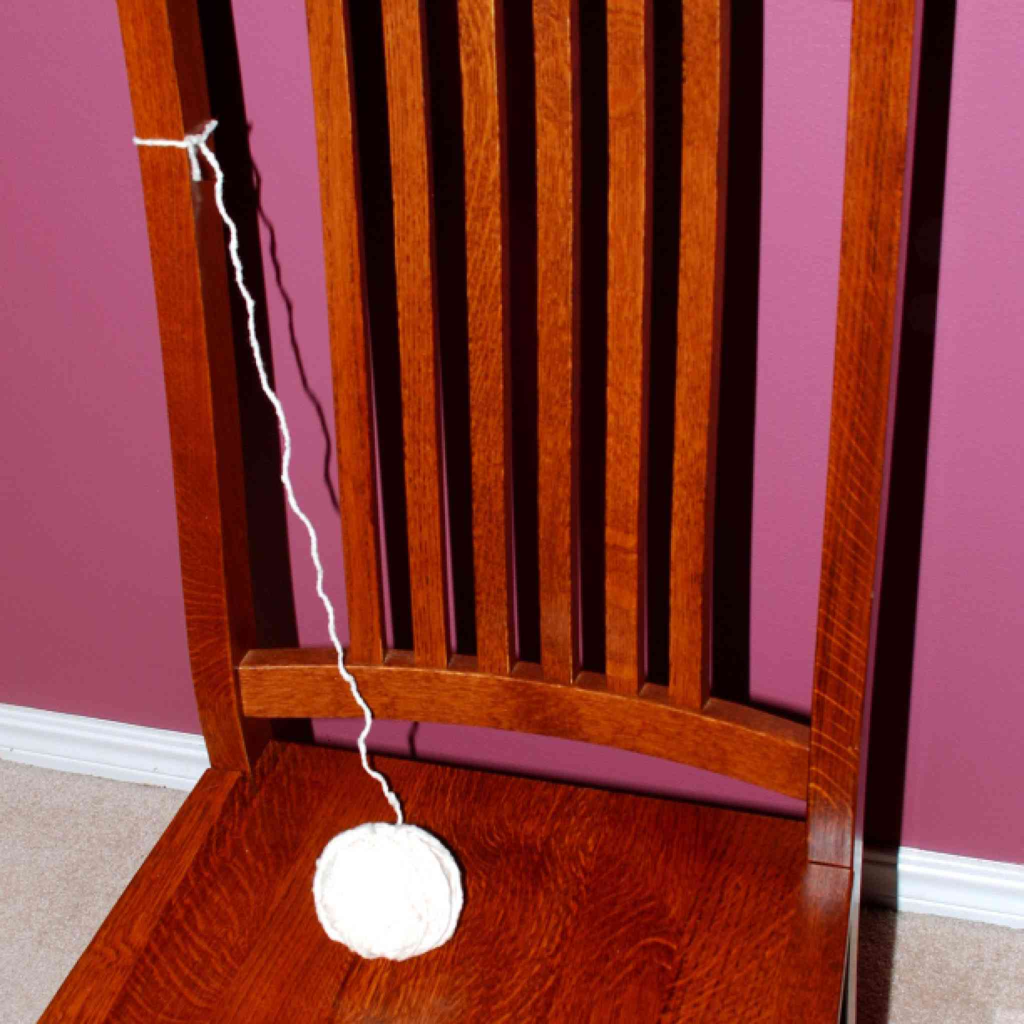 Ball of white yarn tied to a chair.