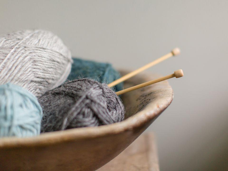 a basket of yarn and knitting needles