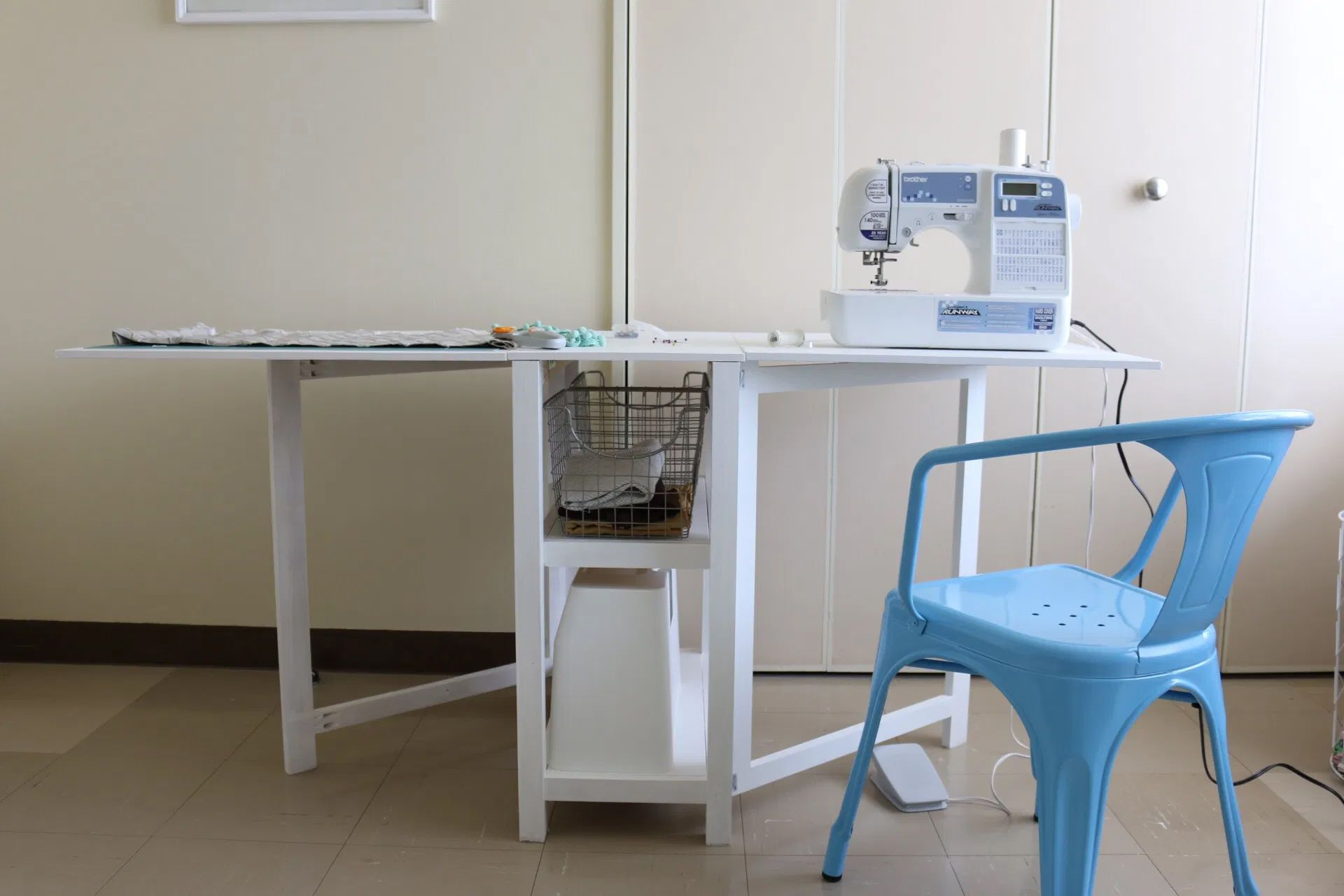 A white sewing desk with a blue chair