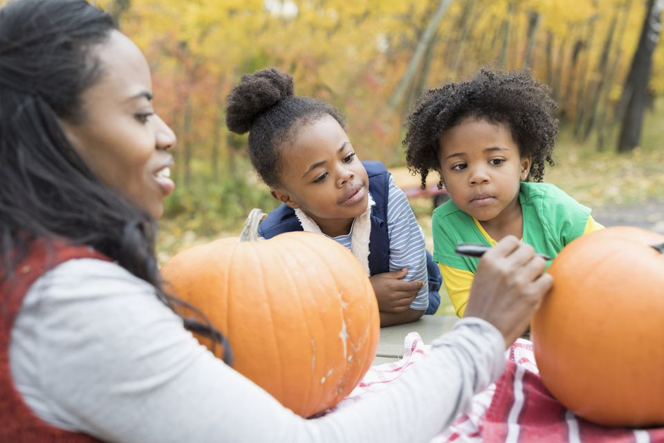 Mother and daughters carving pumpkins