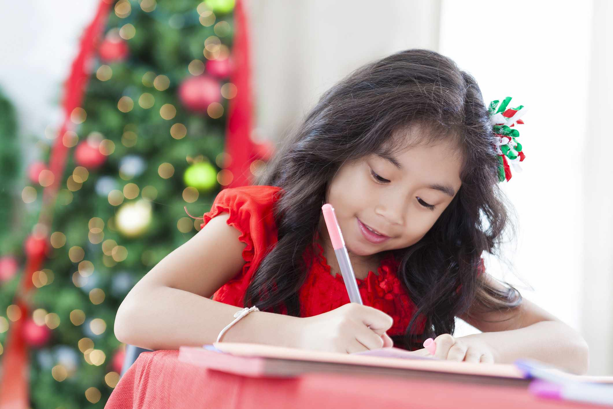 A young girl writing in front of a Christmas tree