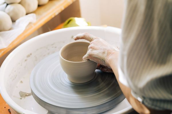 A Woman Potter Scuipting on a Wheel - Making a Cup