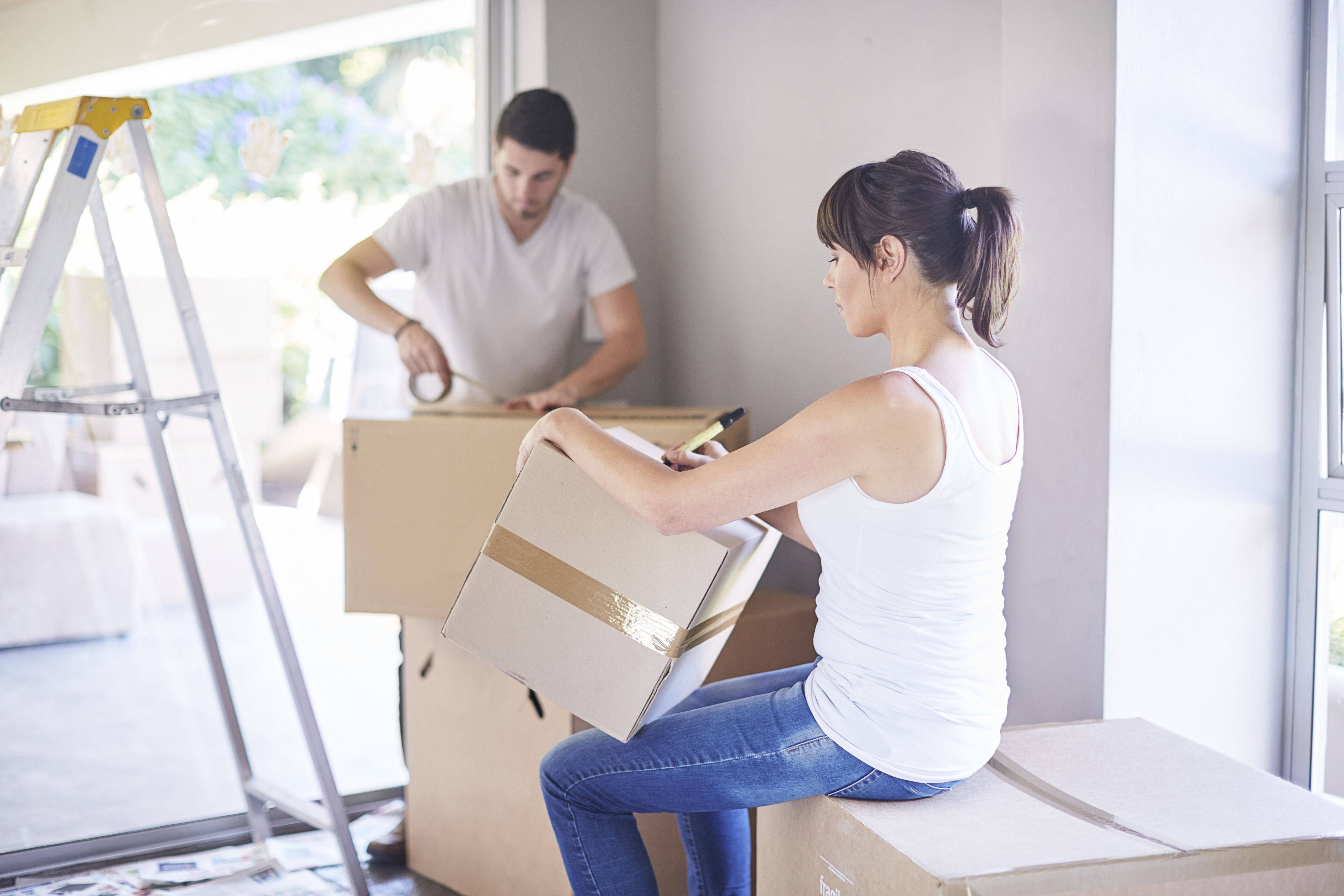 Couple moving house, woman writing on box