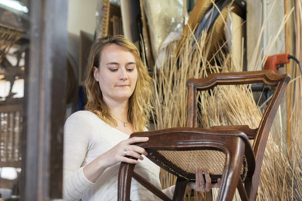 Woman basket maker examining woven seat on dining chair in workshop