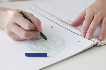 Child drawing picture of earth