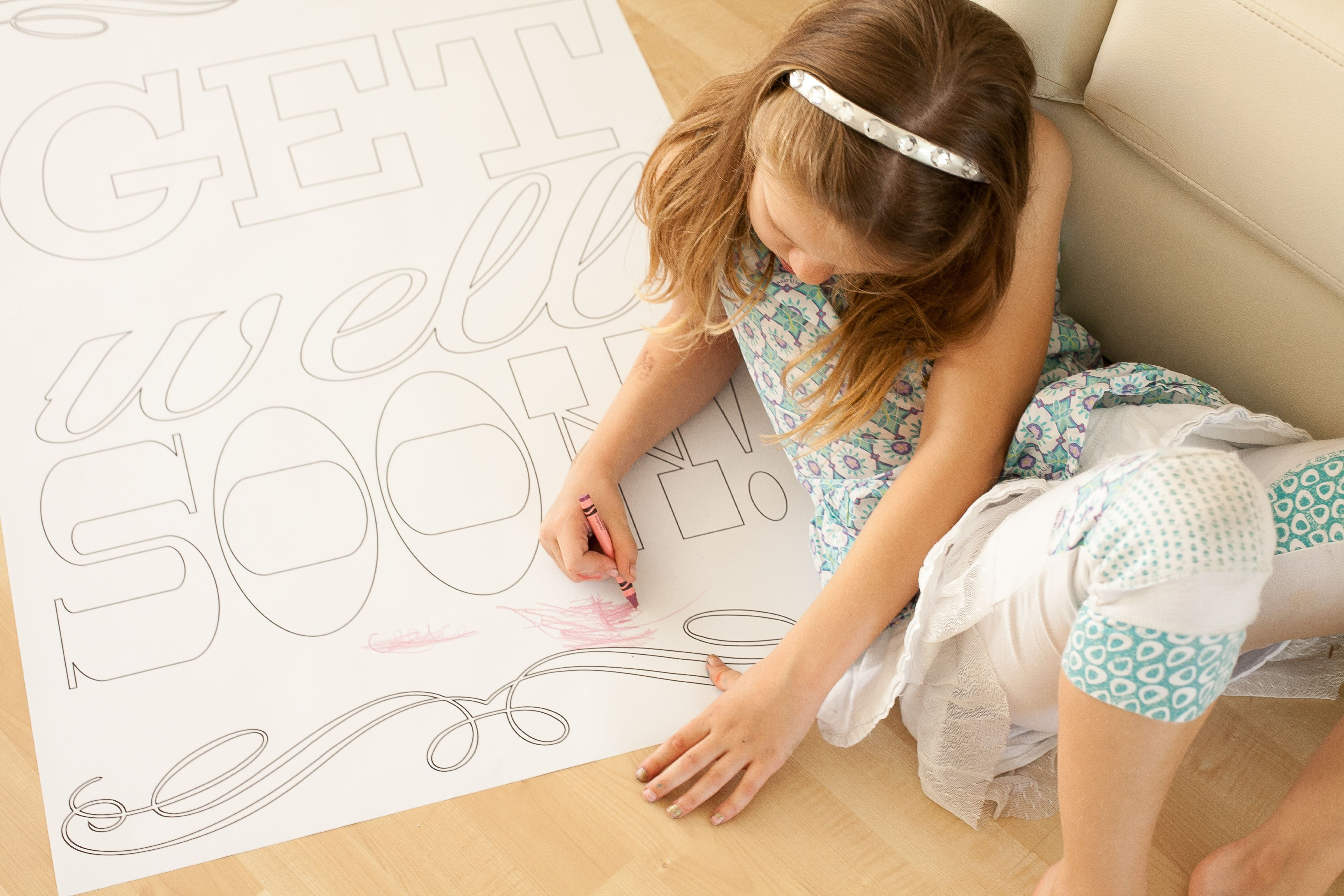 A girl coloring a giant get well soon card.
