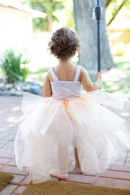 Child facing backwards in a tutu