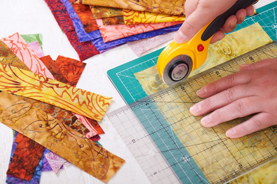 Process cutting fabric pieces by rotary cutter on mat using ruler
