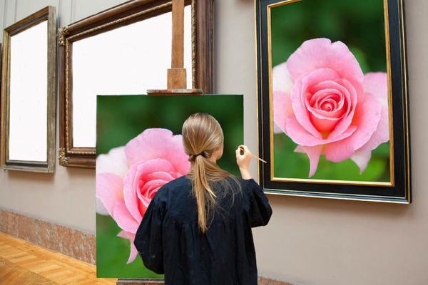 Woman painting a rose from a photo